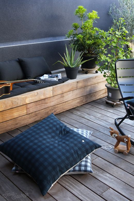 a modern deck with a wooden bench, some dark pillows, potted plants and a metal chair is a small yet cozy spot