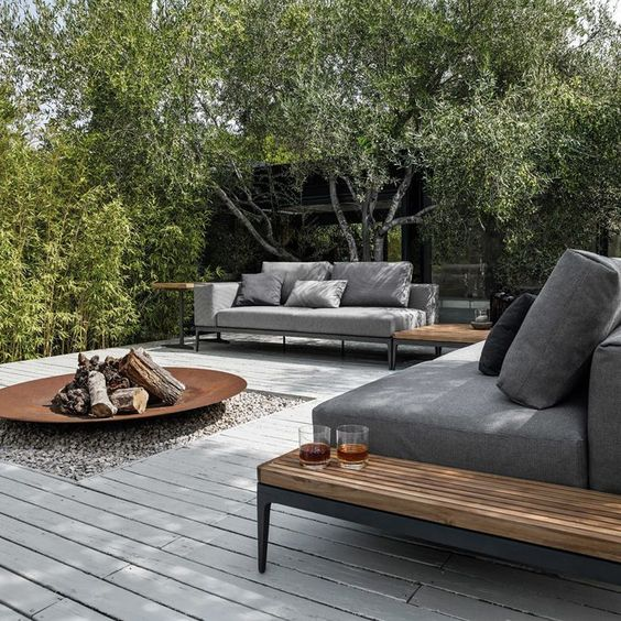 a modern deck with chic grey sofas, wooden tables, a metal fire pit and lots of greenery around is a perfect space to invite guests
