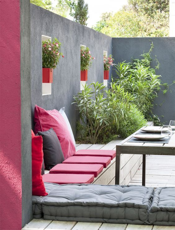 a modern deck with wooden benches, greenery growing, bright pink pillows and a wooden table