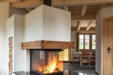 a modern three side fireplace with a glass cover, a black countertop and wooden beams is a stylish piece