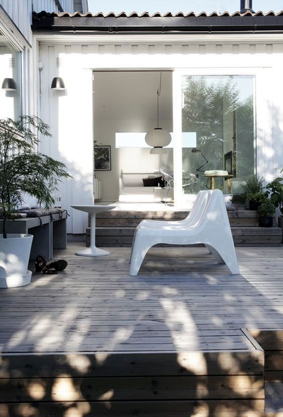 a modern to minimalist deck with a grey bench, some quirky white stools and greenery in pots