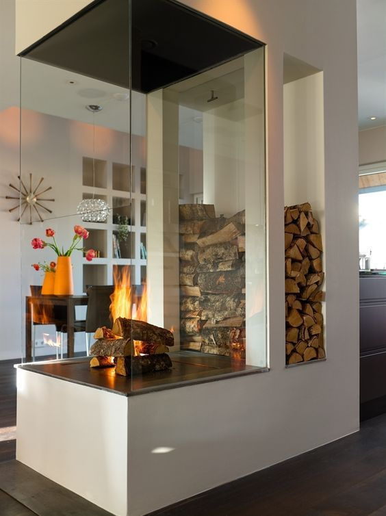 a modern white fireplace with a glass cover and firewoo storage is a nice space divider and is a very cozying up piece