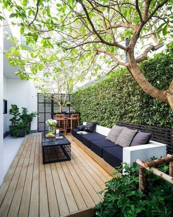 a monochromatic deck with a living wall, a bar space, a large black sofa and a black table plus candles