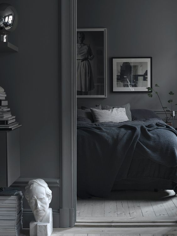 a moody Nordic bedroom with grey walls, a monochromatic gallery wall, dark bedding and potted greenery