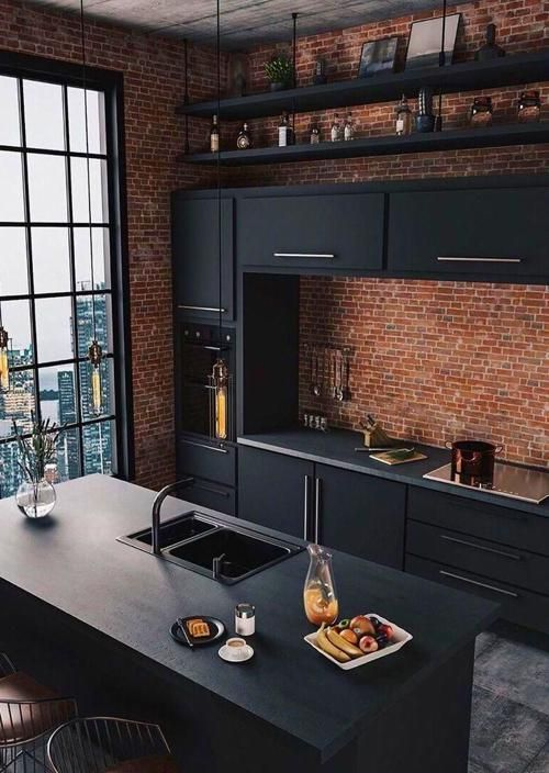 a moody and bold kitchen with red brick walls, sleek black cabinetry, black shelves and pendant lamps hanging