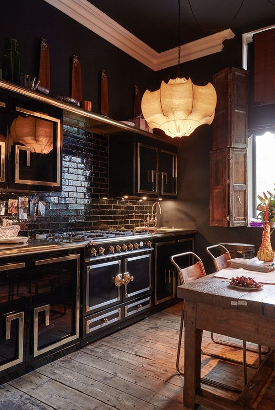 a moody and glam kitchen with black cabinetry, metallic patterns, a black tile backsplash, a pendant lamp, a rough table and leather chairs