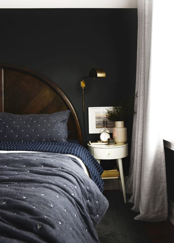 a moody bedorom with dark walls, a dark wooden bed, navy and blue bedding, a round nightstand and some greenery
