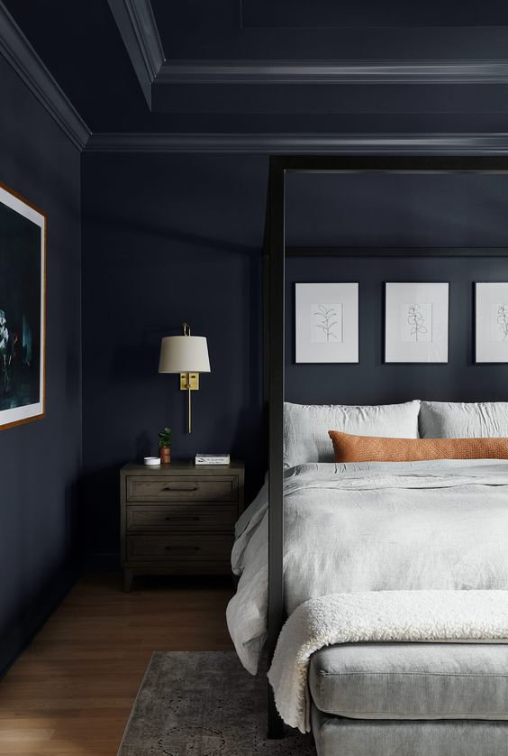 a moody bedroom with navy walls, a cnaopy bed, neutral textiles and a gallery wall, lamps on the nightstands