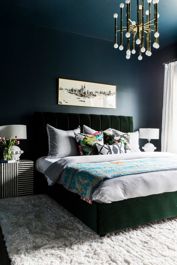 a moody bedroom with navy walls and a ceiling, a dark green velvet bed, a glam gold chandelier and striped nightstands
