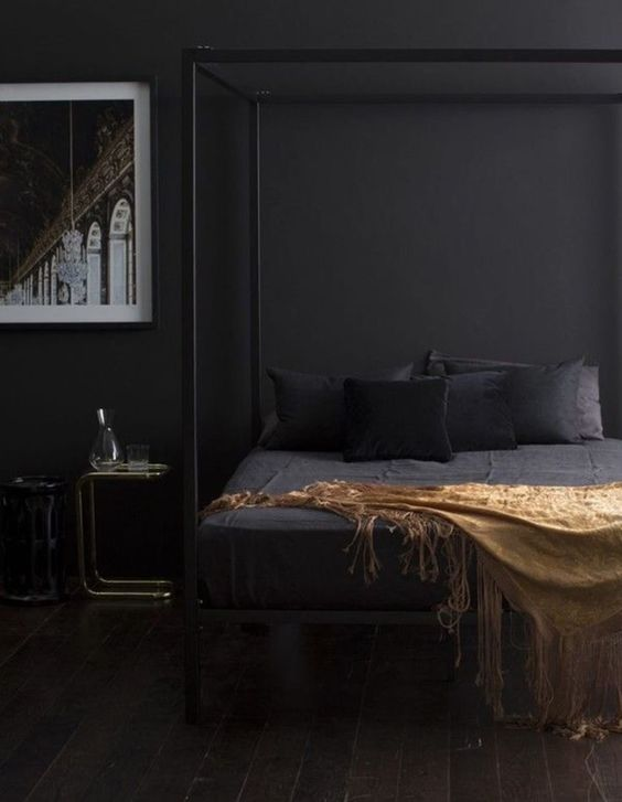 a moody contemporary bedroom with black walls, a black cnaopy bed, chic nightstands and a bold artwork