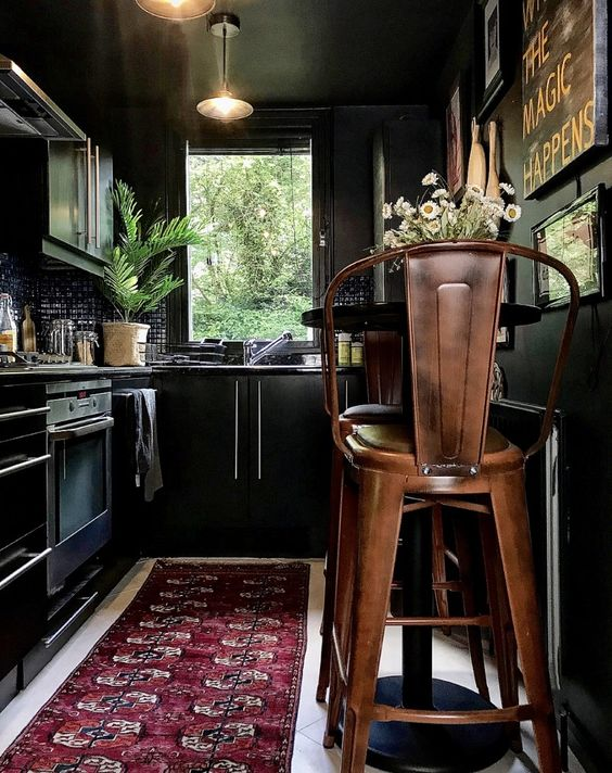 a moody kitchen in black, with black walls, cabinetry, a black tile backsplash, a boho rug, metal chairs and greenery and blooms