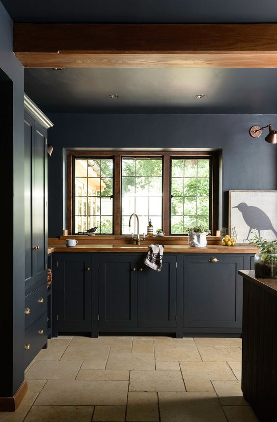 a moody kitchen wiht black cabinetry, wooden countertops, wooden frames and beams, metallic handles and an artwork