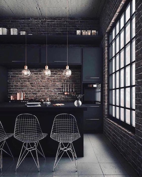 a moody kitchen with black cabinetry, brick walls for a strong industrial feel, metal chairs, round pendant lamps