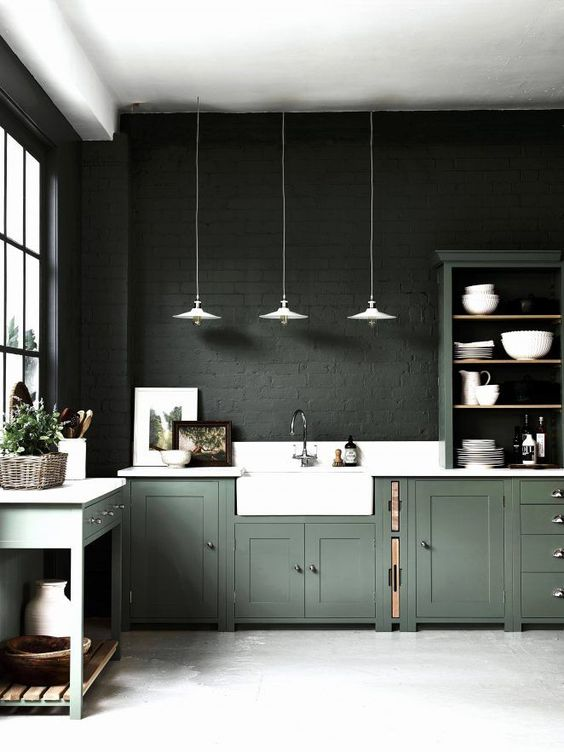 a moody kitchen with dark green brick walls, green cabinetry, white countertops and white pendant lamps is a statement