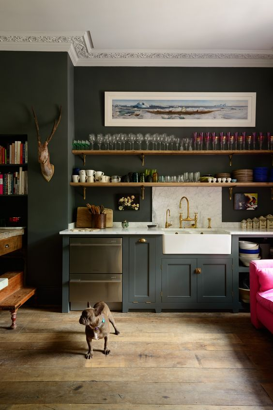 a moody kitchen with graphite grey cabinets, white marble countertops, shelves, molding and dark furniture plus an artwork