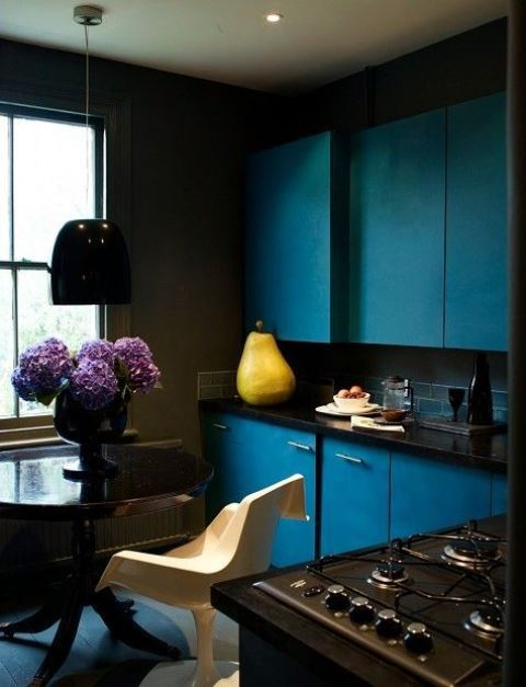 a moody kitchen with navy cabinetry, black coutnertops, a navy tile backsplash, dark furniture and a pendant lamp