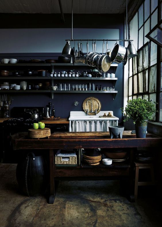 a moody kitchen with navy walls, dark cabinetry, a rough wooden kitchen island, metal shelves and a holder with pans