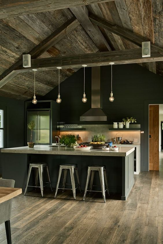a moody kitchen with rustic and industrial touches, black walls and cabinetry, neutral countertops, pendant lamps and a neutral tile backsplash
