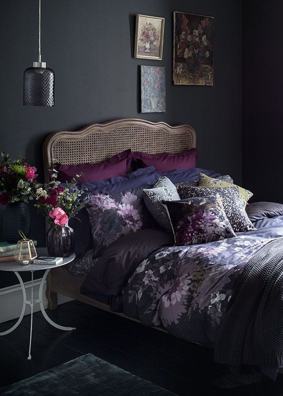 a moody vintage bedroom with black walls, a rattan bed, a gallery wall, a little nightstand and a pendant lamp