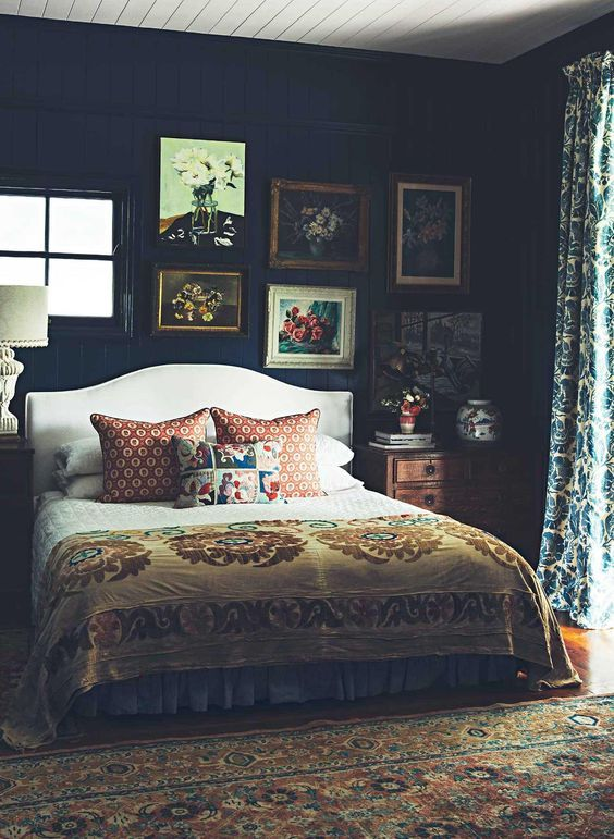 a moody vintage bedroom with dark walls but a light ceiling, a cofy bed and vintage furniture, a gallery wall and printed textiles