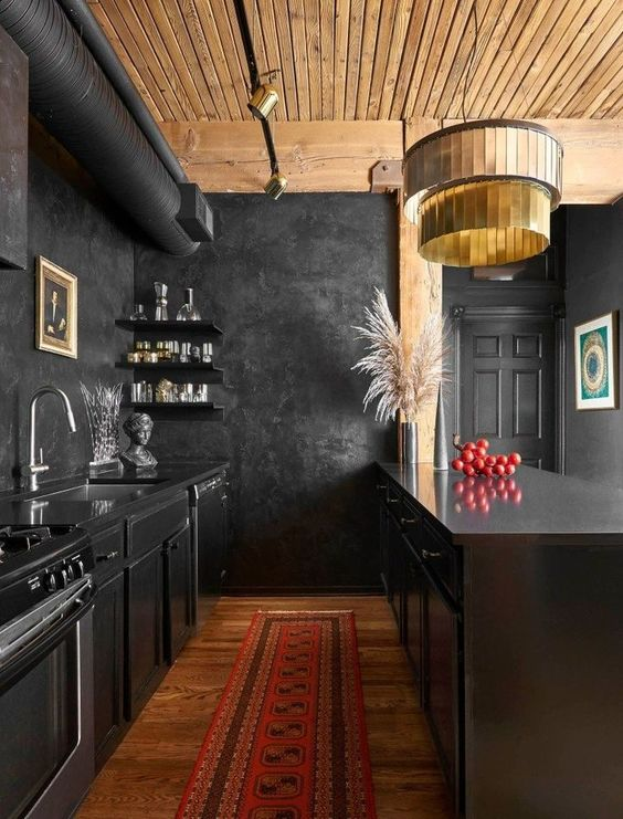 a moody yet bold kitchen with black cabinetry, black walls, a wooden ceiling, a gold chandelier and pampas grass in a vase