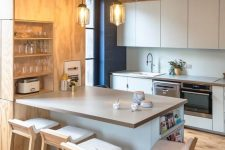 a neutral contemporary kitchen with white cabinetry, a plywood storage unit that continues to the ceiling, stools at the table