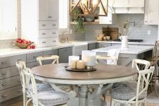 a neutral farmhouse kitchen with grey and white cabinetry, a pendant lamp, a large round wooden table and chairs