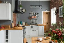 a neutral farmhouse kitchen with white cabinetry, wooden countertops, a brick backsplash, a wooden table and chairs