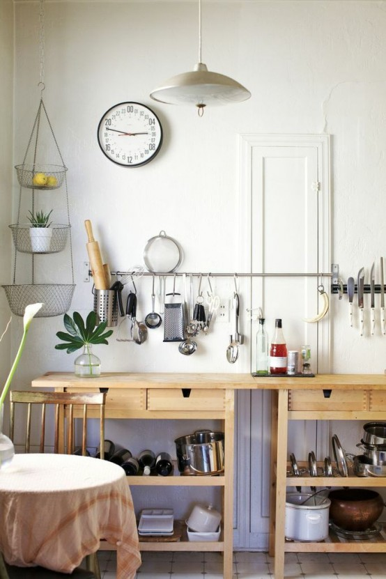 a neutral kitchen cooking space of two IKEA Forhoja carts and long railing for hanging things