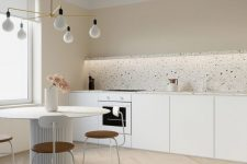 a neutral minimalist kitchen with a terrazzo backsplash, a round table, whimsy chairs and a minimal chandelier over the dining space