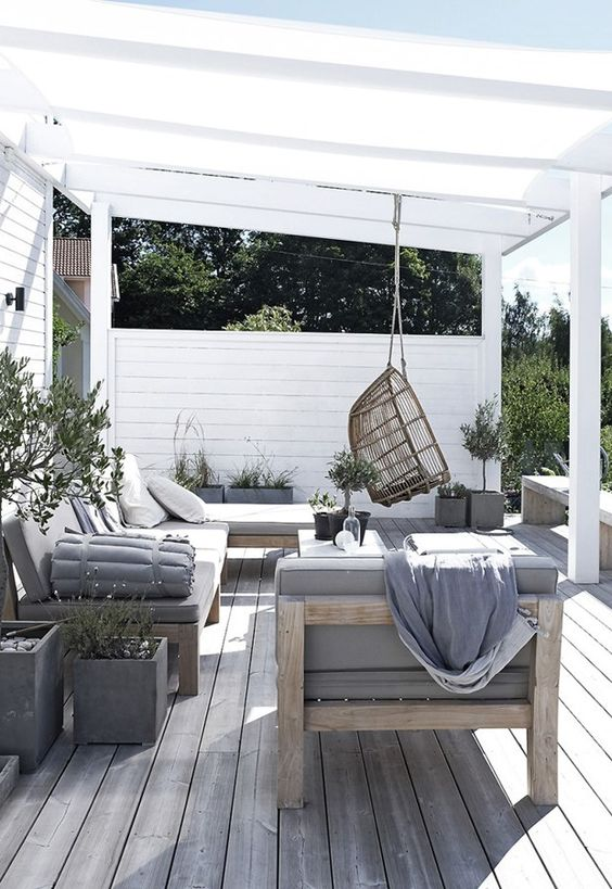 a neutral wood modern deck with light-colored wooden furniture, grey upholstery, a suspended chair and greenery
