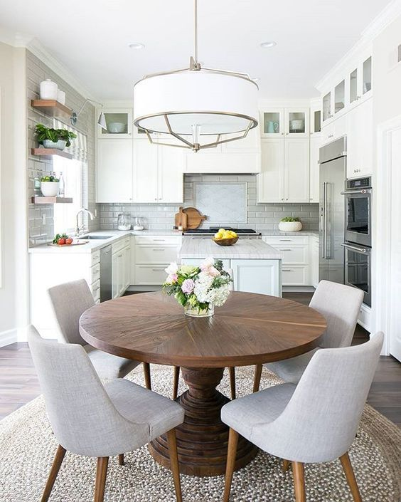 a neutral modern farmhouse kitchen with a pendant lamp, a round table and grey chairs is a very welcoming space