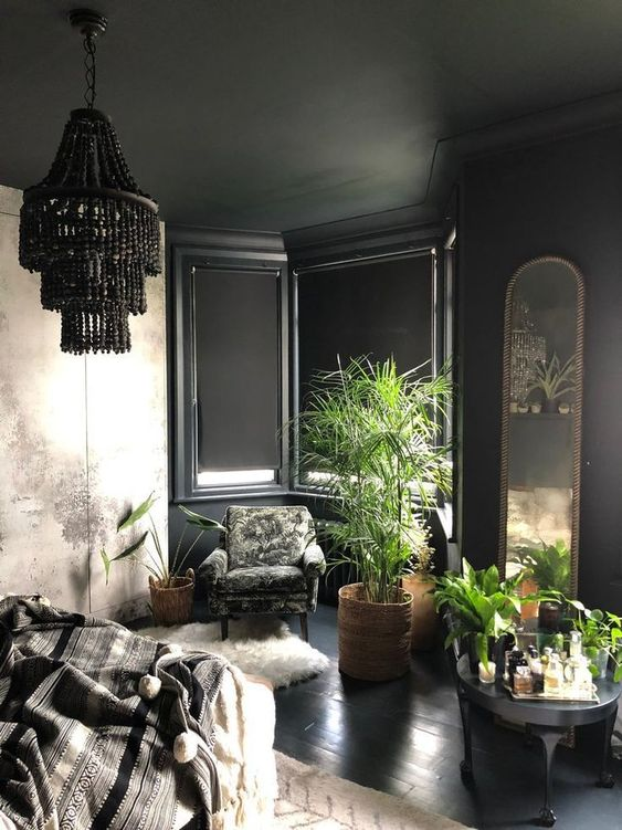 a refined black bedroom with a bay window, a black beaded chandelier, potted plants, faux fur and an arched mirror