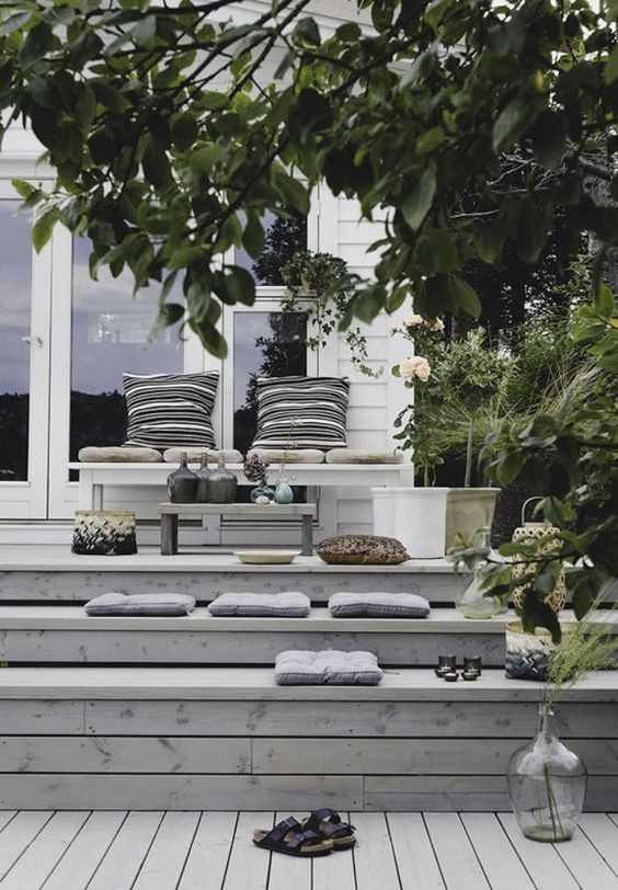 a simple deck with a bench, lots of cushions placed right on the steps to avoid using furniture, candles and greenery