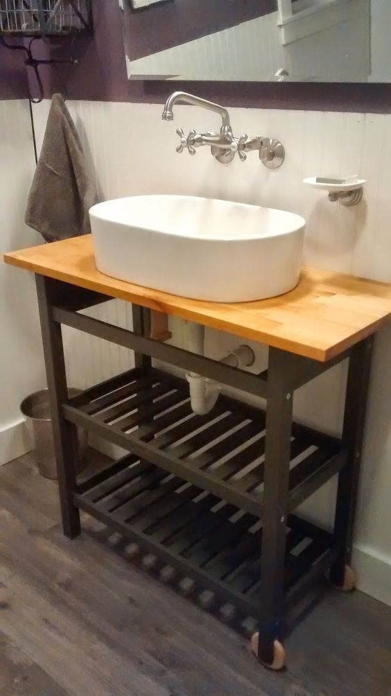 a simple farmhouse bathroom vanity made of an IKEA Forhoja cart hacked with black paint and a butcherblock countertop