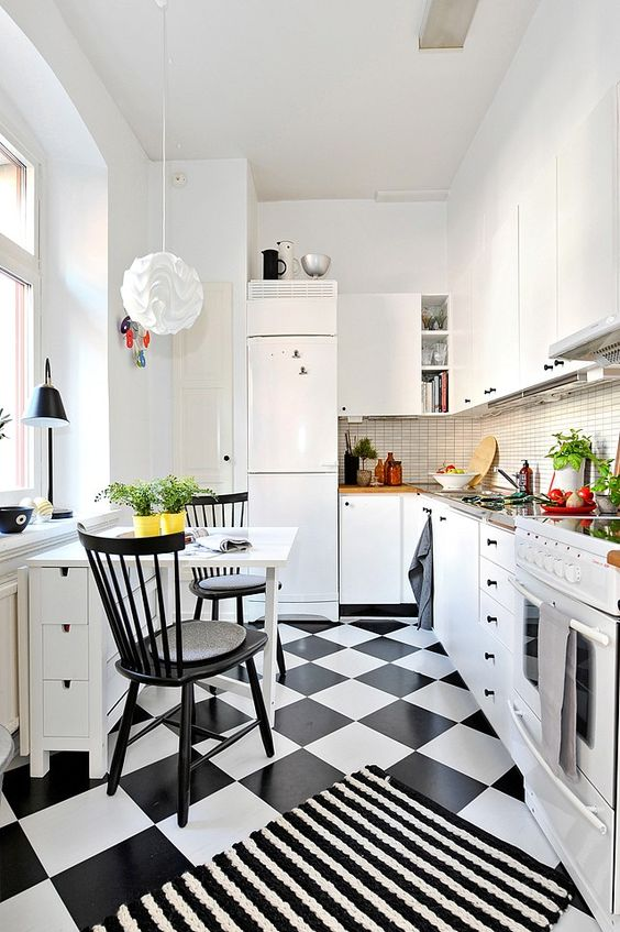 a small bold kitchen with white cabinetry, a skinny tile backsplash, a quirky pendant lamp, a black and white floor and a small dining zone