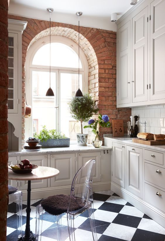 a small farmhouse kitchen with neutral cabinets, a brick wall, a round table, acrylic chairs and pendant lamps