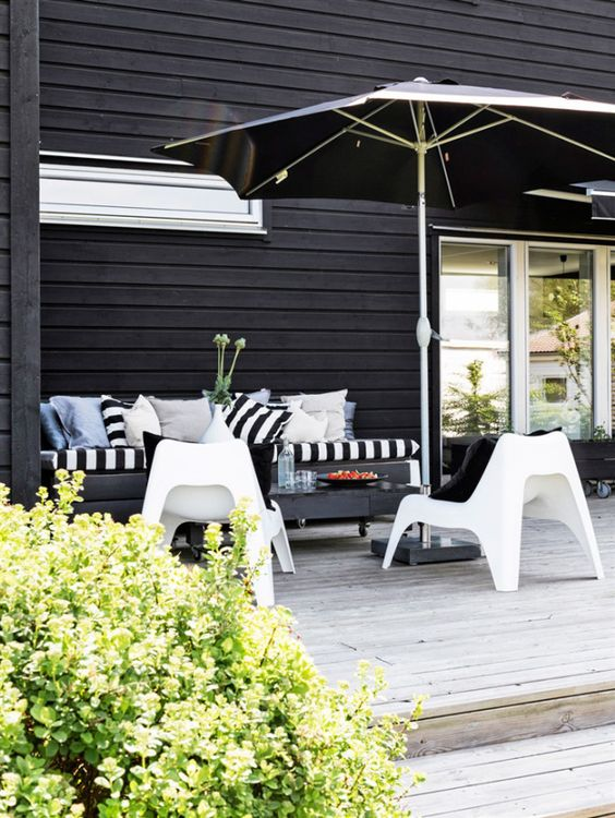 a small modern deck with a black bench, white chairs, a black table on casters and a black umbrella