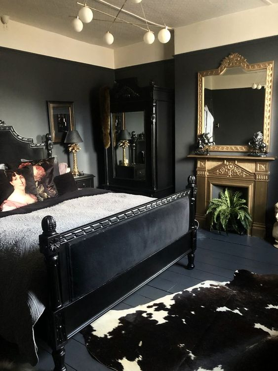 a sophisticated bedroom with black walls, a black bed and mirror, a gold fireplace and a mirror and some plants and art
