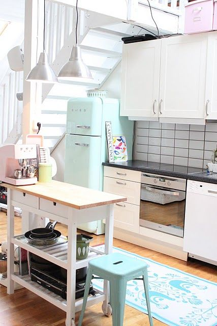 a space saving kitchen island of an IKEA Forhoja cart painted white and with a wooden countertop