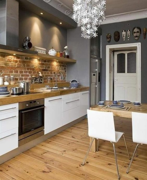a stylish Scandinavian kitchen with white cabinets, wooden countertops, a brick backsplash, a floral chandelier, white chairs and a wooden table