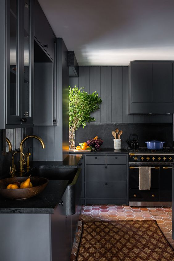 a stylish and refined moody kitchen with black cabinetry, a black backsplash, gold faucets for a chic touch