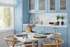 a stylish blue kitchen with a white tile backsplash and a dining zone with a round table and wooden chairs with striped cushions