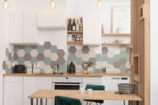 a stylish contemporary kitchen in white, with grey, green and neutral hex tiles, green chairs and a small hairpin leg table