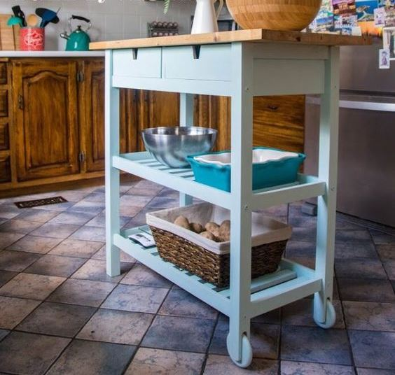 a stylish farmhouse kitchen island of a light blue IKEA Forhoja cart with a wooden countetop