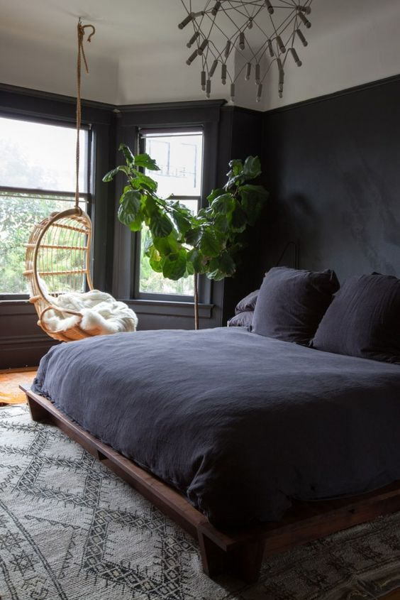 a stylsh modern moody bedroom in black, with a pendant chair, a dark wooden bed and a cool chandelier, a statemtn plant in a pot