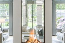 a two sided fireplace with glass will provide two spaces with a beautiful fire look and with coziness and chic