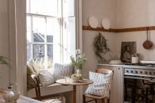 a vintage-inspired neutral kitchen with light colored wooden cabinets, a cozy dining space with a windowsill seat, wooden chairs and a table