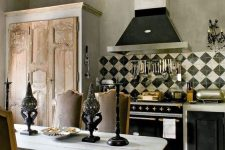 a vintage kitchen with black and white cabinets, a crystal chandelier, a wooden table, vintage chairs and candleholders plus a modern clock