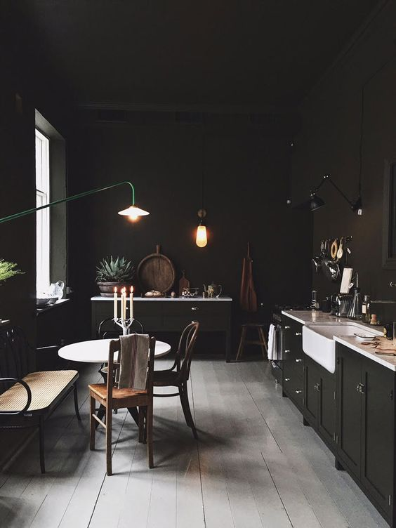 a vintage moody kitchen done in black, with black walls and cabinetry, white countertops, a round table and mismatching chairs